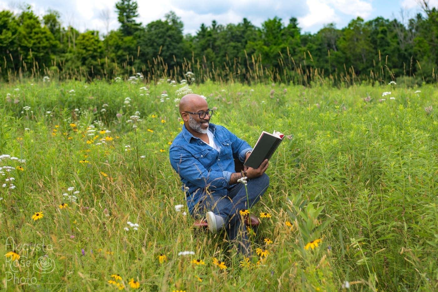 Ty Allan Jackson reading in a field